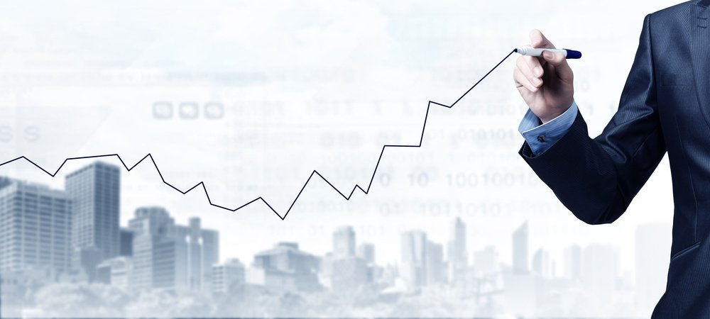 Close up of businessman drawing increasing graph with marker