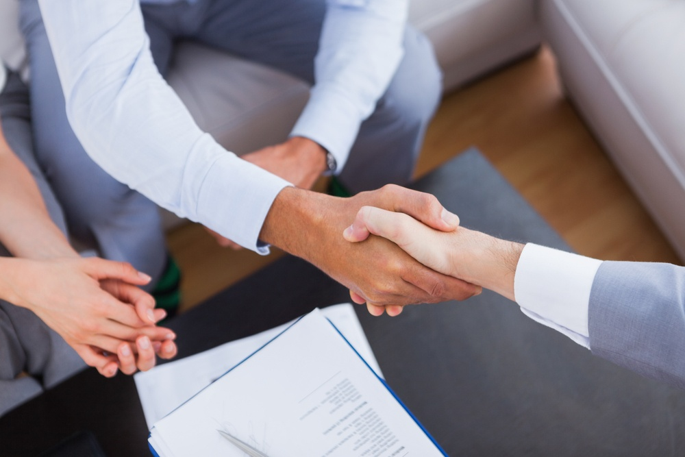 Salesman shaking hands with client with contract on the coffee table